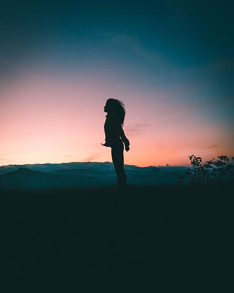 Person i siluett framför solnedgång och berg