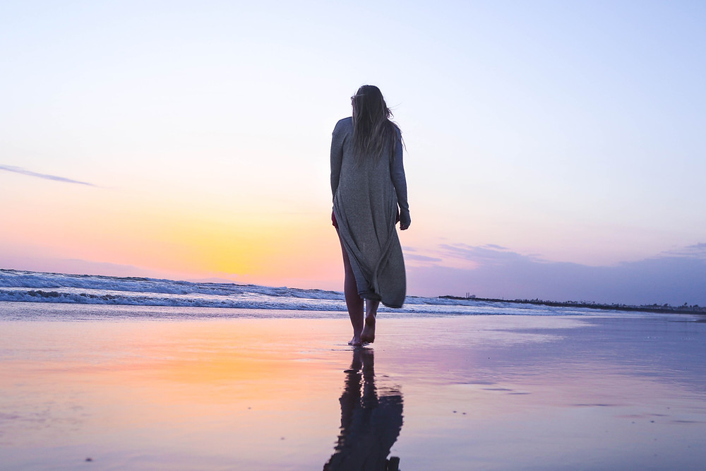 Woman walking on wet sand at beach at sunset, wearing long white coat.