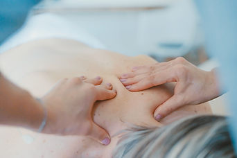 Woman with grey hair lying face down on a treatment table and a womans hands massaging her upper back