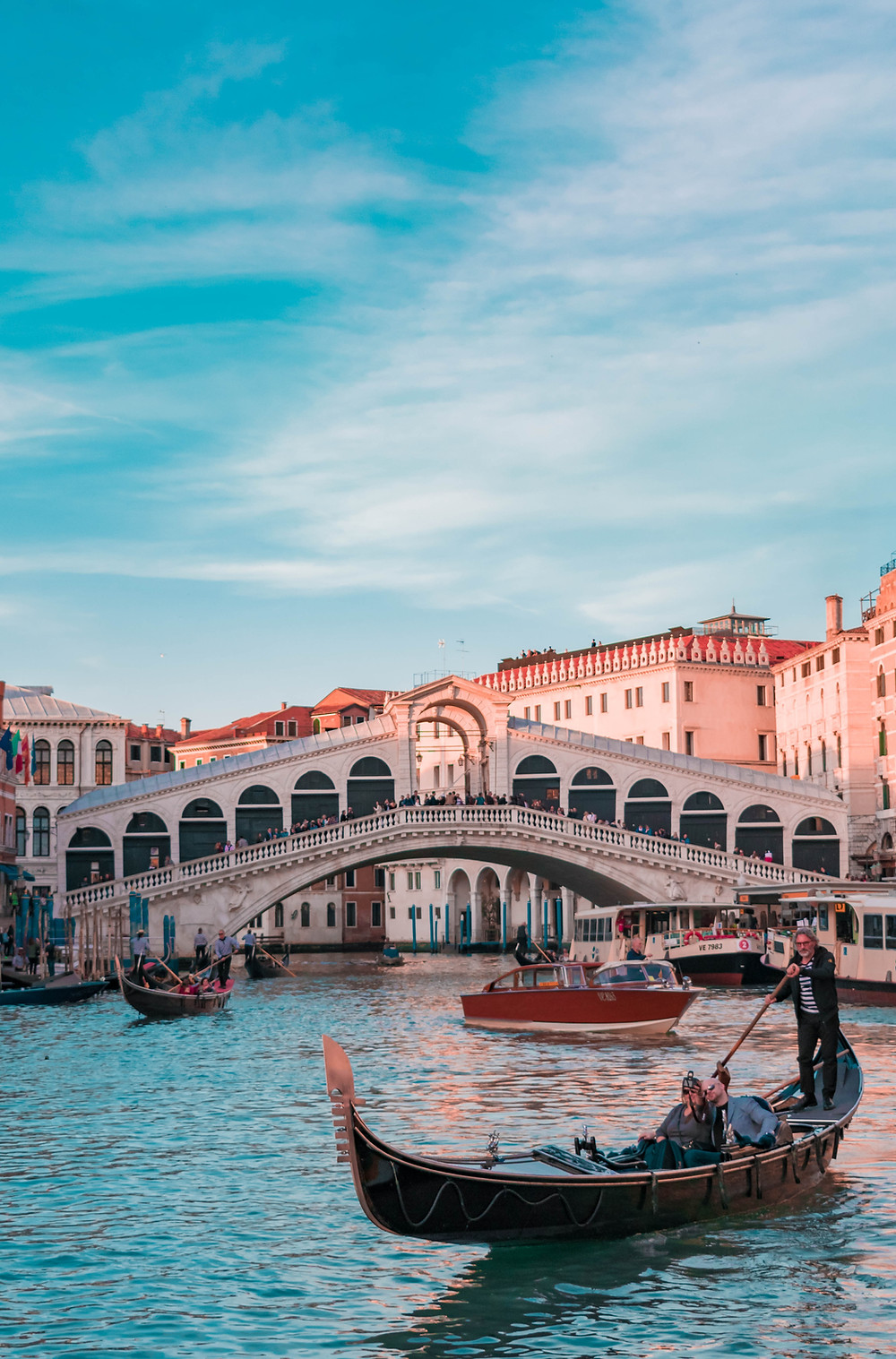 View of the Rialto Bridge in Venice, with a gondola in the foreground and blue skies above