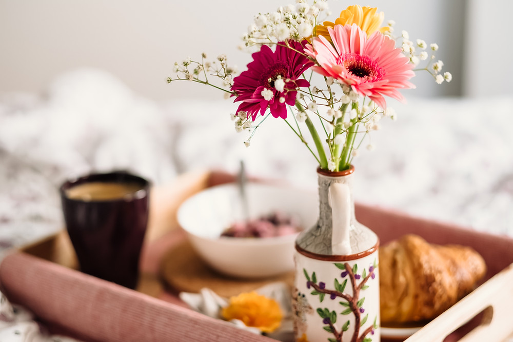 vase of flowers with breakfast in bed tray