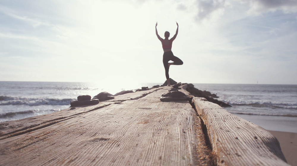 Woman standing on log at the end of beach feeling good