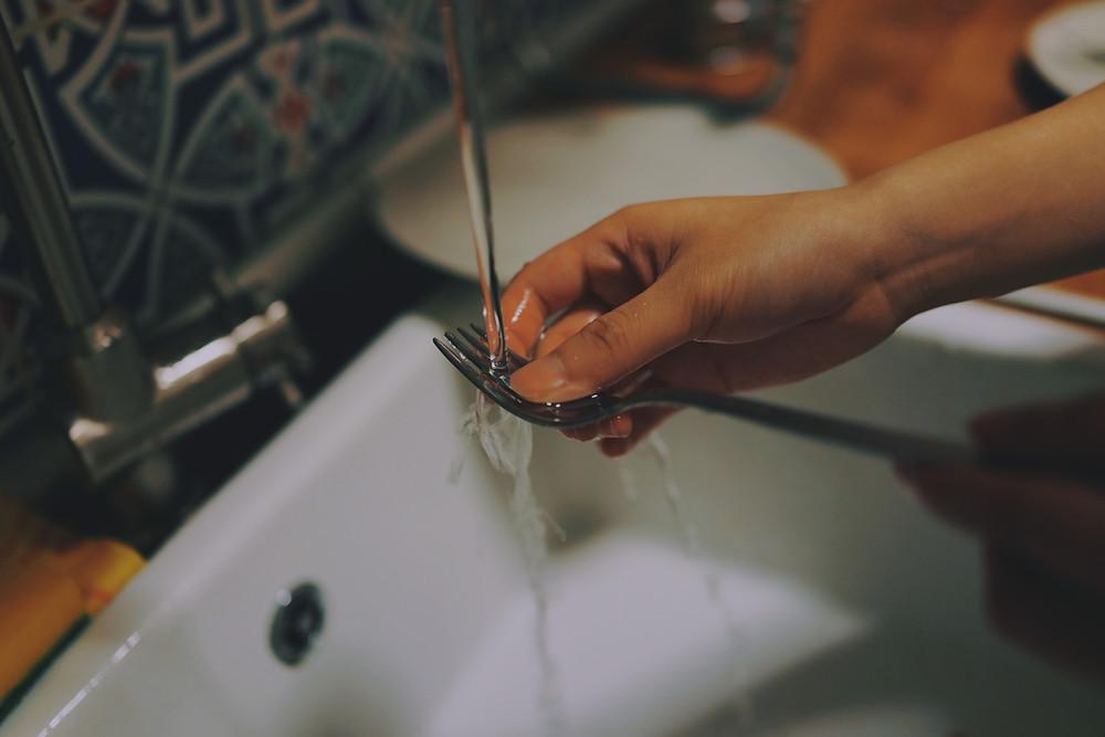 Rinsing fork under running tap water