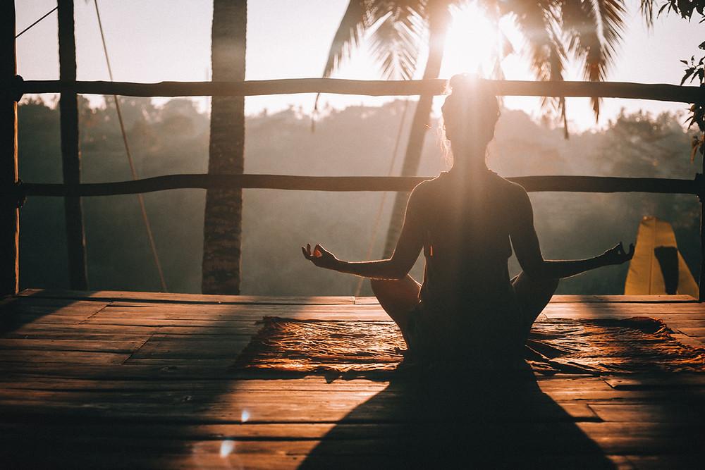 Woman meditating at sunrise.