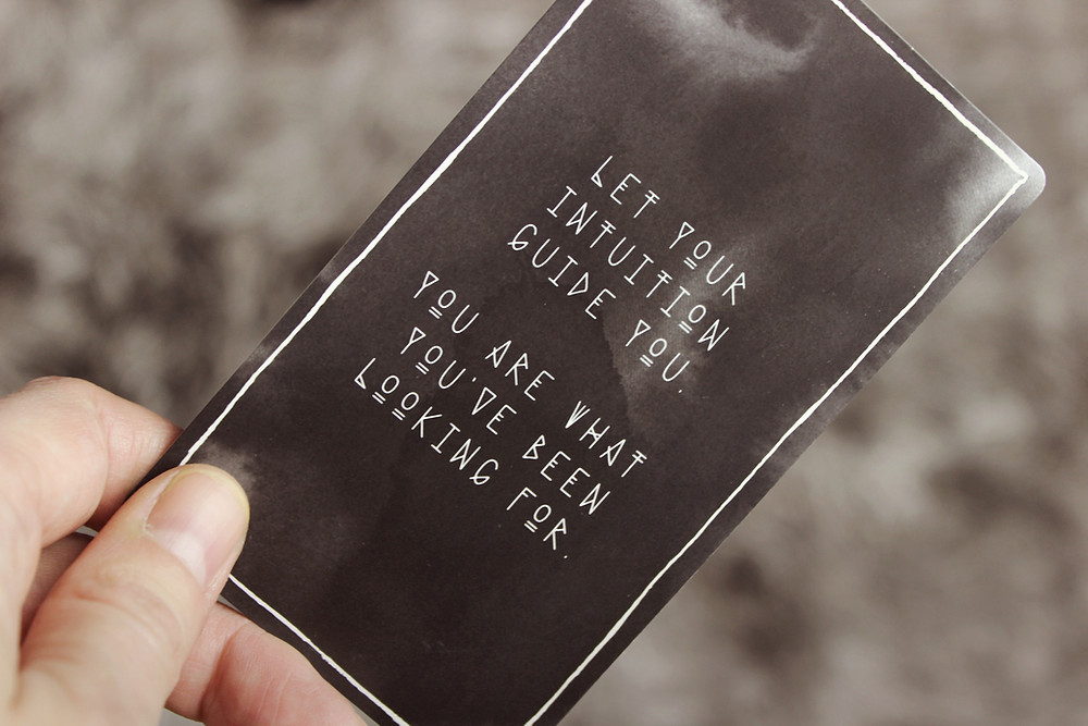 Hand holding black card that reads 'Let your intuition guide you. You are what you've been looking for'