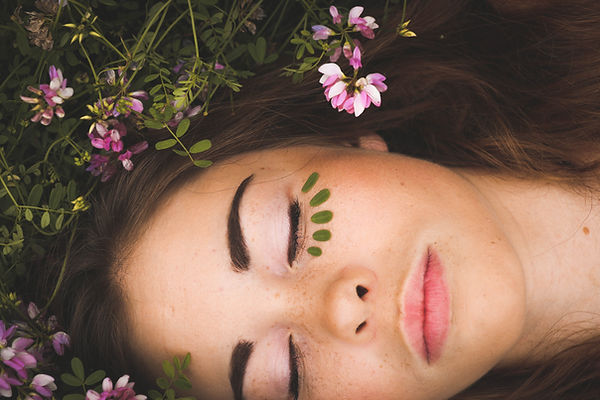 Woman's face, eyes shut, flowers in her hair