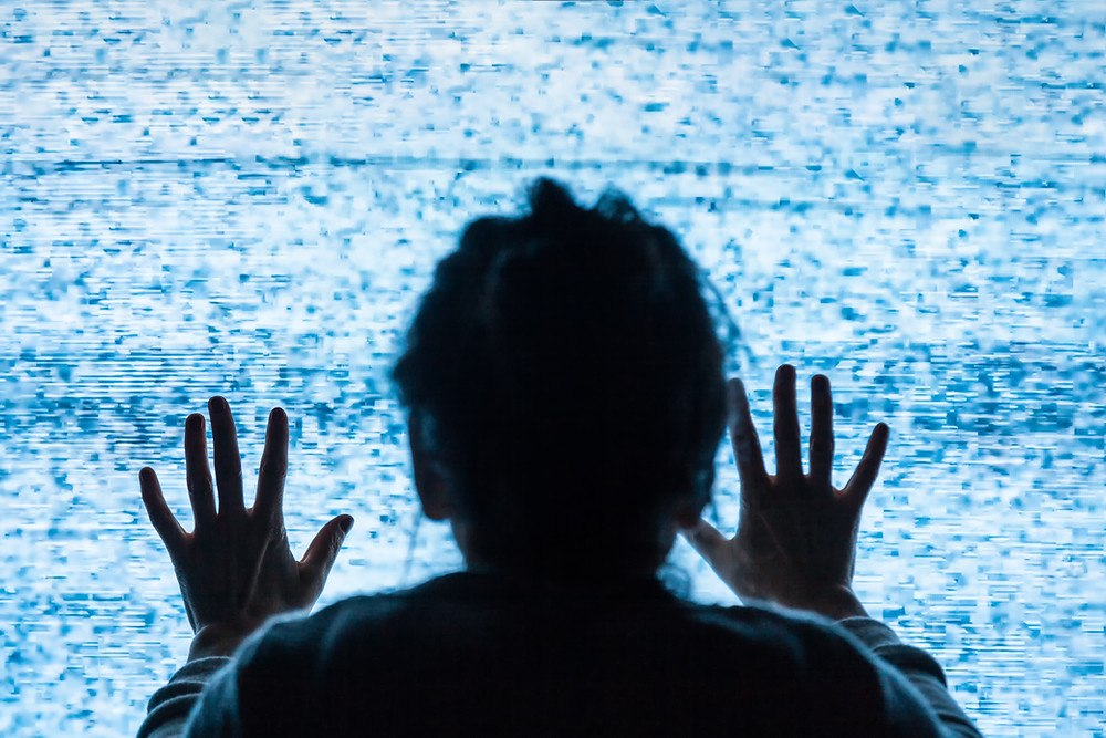 older woman with hands on tv screen static showing depicting alzheimers, memory loss