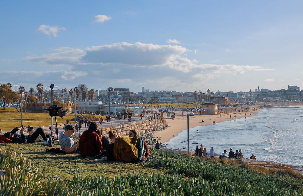 Friends sitting on a beach hill overlooking the sea in Tel Aviv