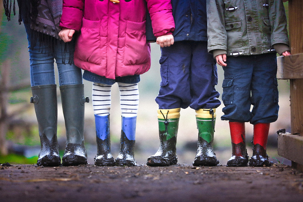 Mom with kids in colorful rain boots escape their house during quarantine.