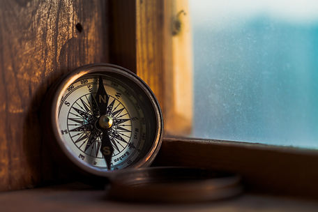 Photograph of a bronze, black and white compass leaning against a wooden window frame. Image is by Jordan Madrid via Unsplash.