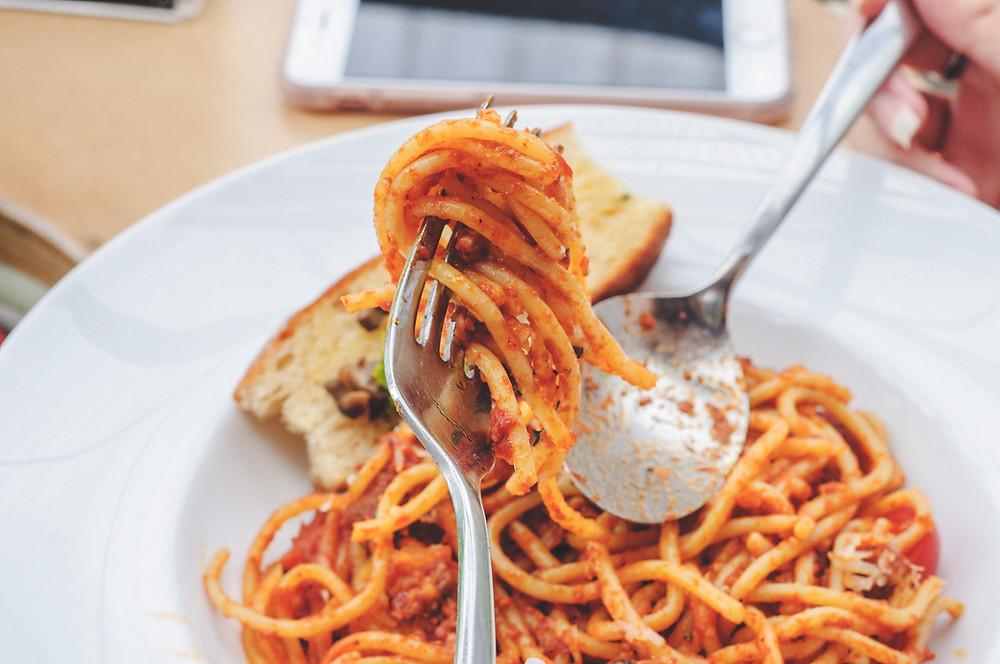 prato com massa ao sugo, em primeiro plano mão feminina segura um garfo, ao fundo imagem de um celular