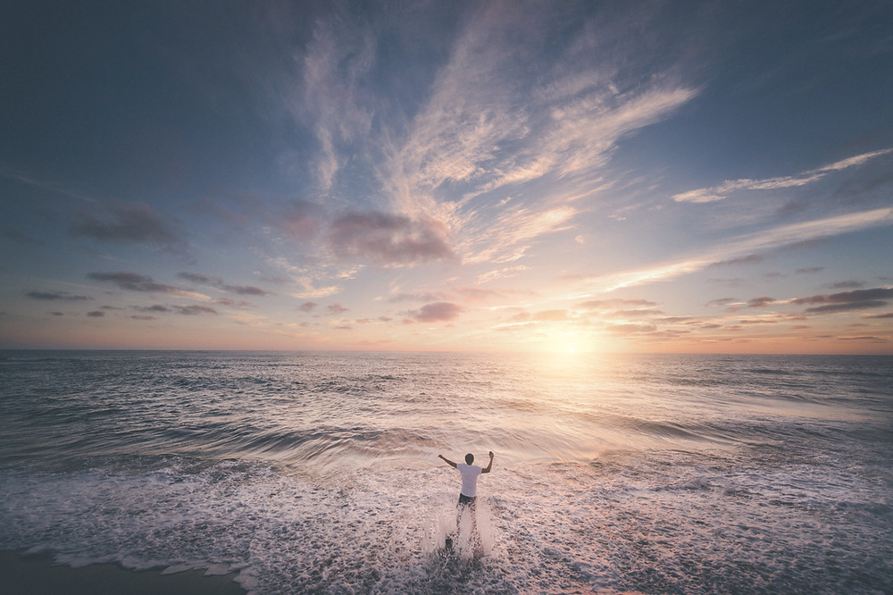 A person enjoying the beautiful sunrise at the beach, standing in the sea and feeling energised