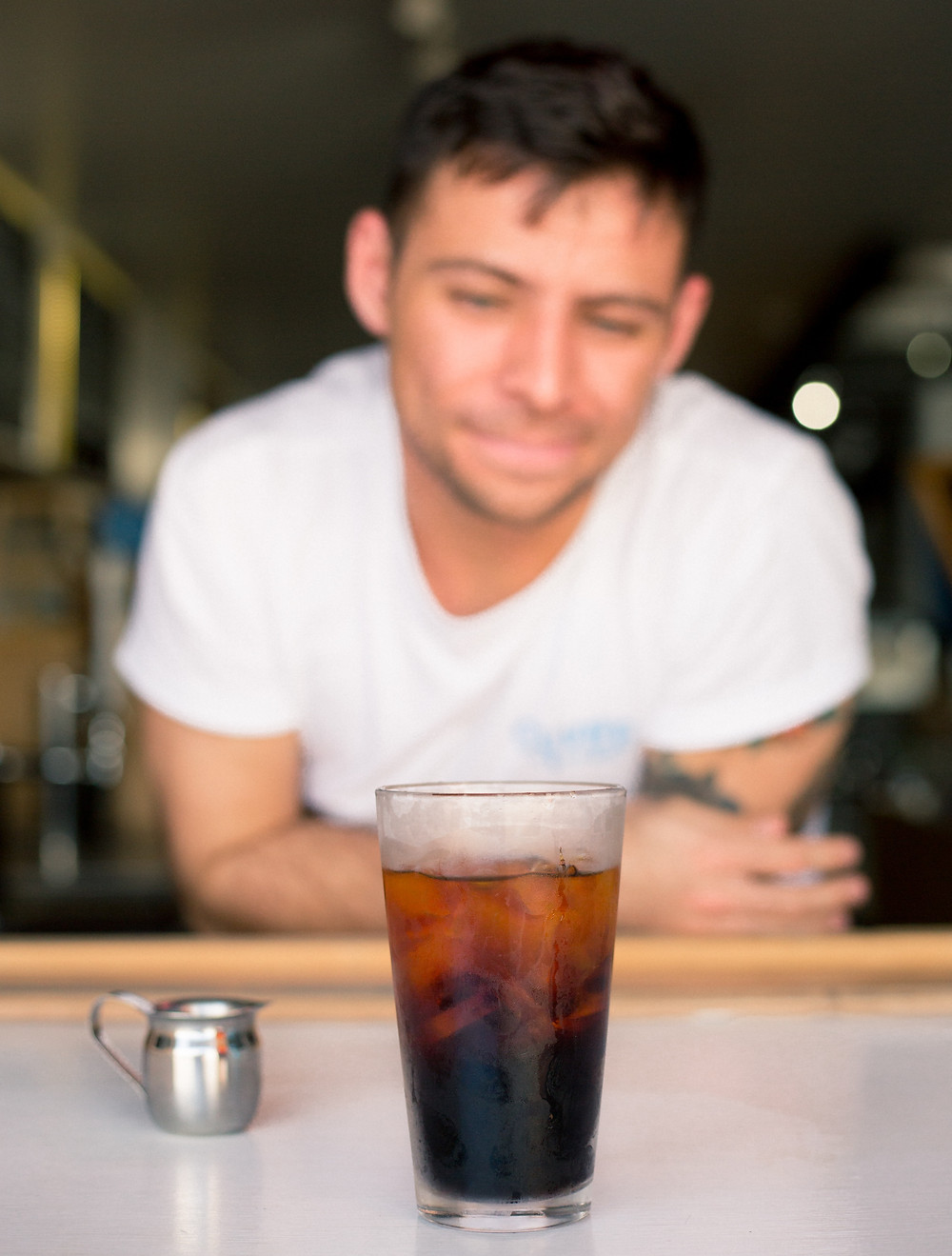 mężczyzna patrzy na szklankę kawy z lodem