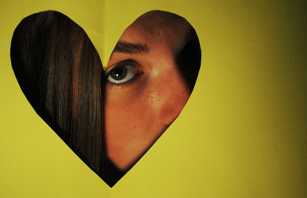 Part of a face behind a heart shape cutout