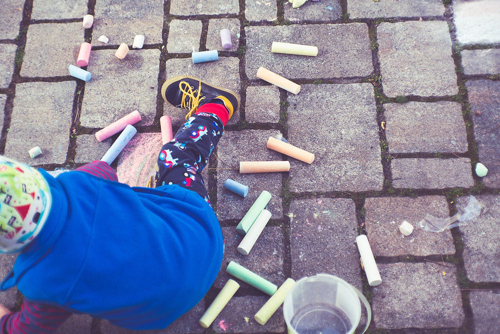 Child in colourful outfit, seated on uneven brick ground, with coloured chalk of different sizes scattered around