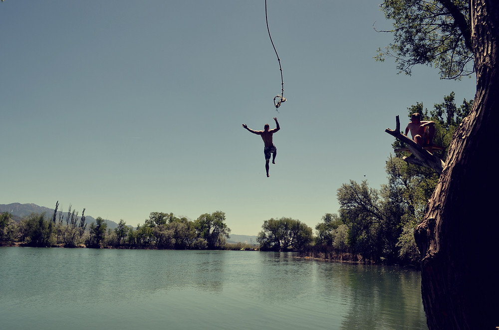 Man letting go of a rope over a lake