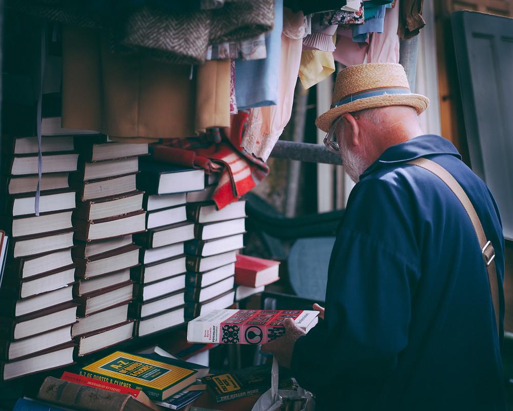 senhor escolhendo livro entre muitas pilhas