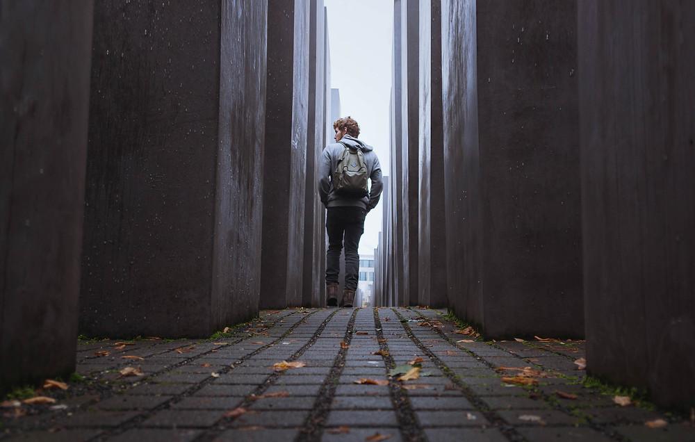 בחור צעיר מטייל בין האבנים של אנדרטת השואה