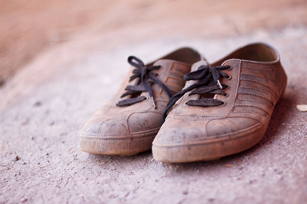 Pair of old smelly shoes on the dirt