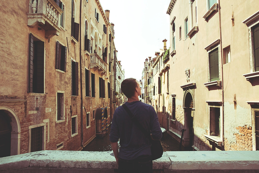young man looking at Italian buildings
