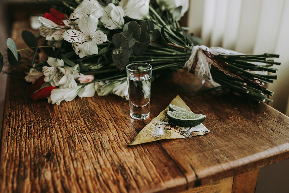 shot of tequila on old wooden table next to floral bouquet