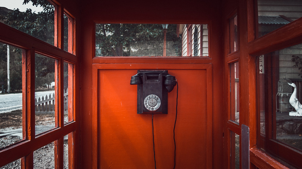 Old black phone in a red phone booth.