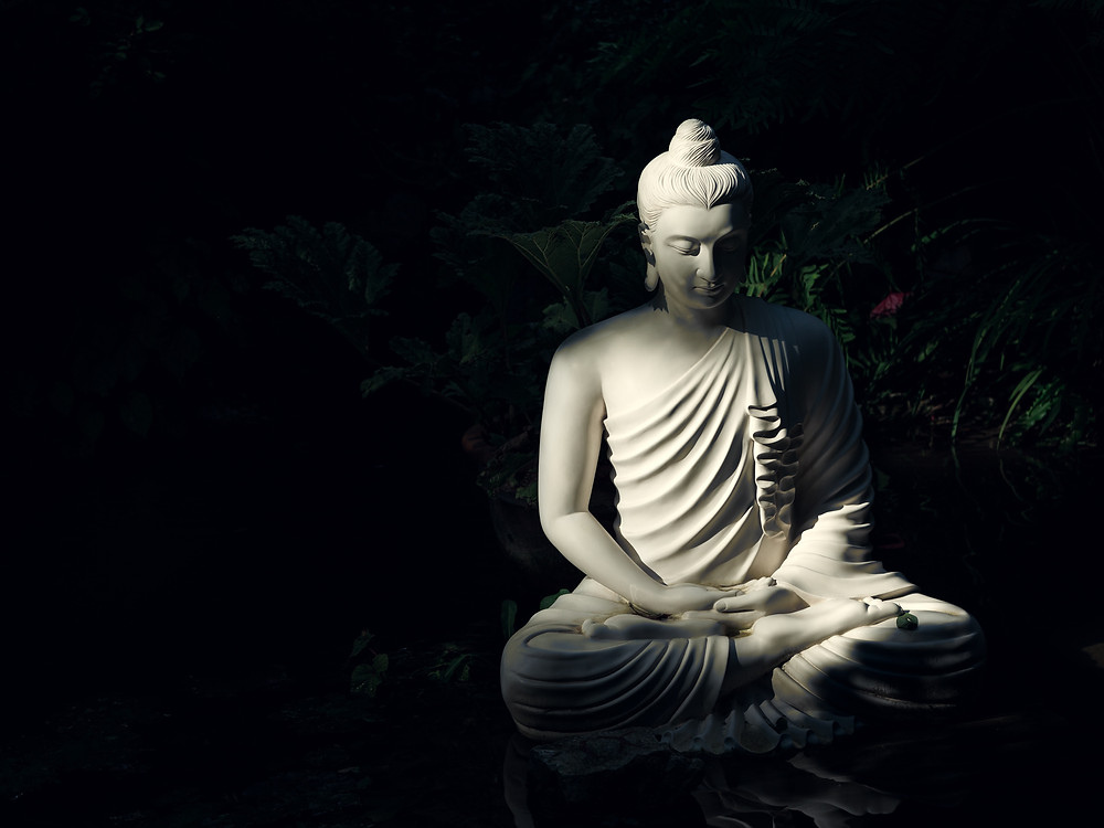 a white statue of Buddha in lotus pose against a black background