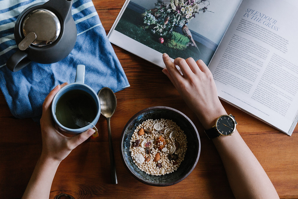 a woman reading a book while eating healthy