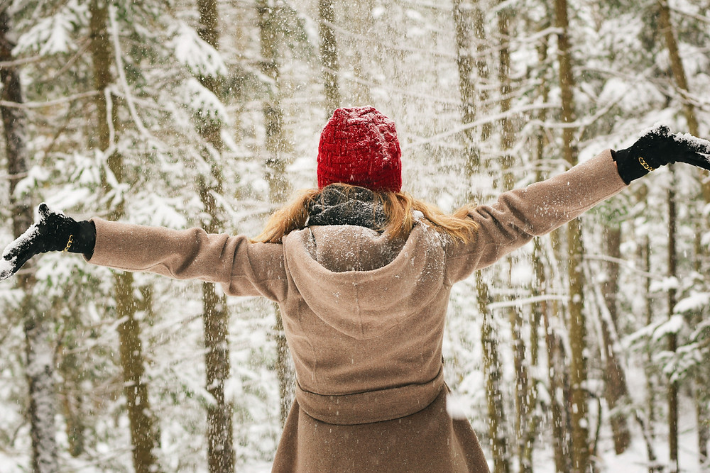 woman with arms out in snow