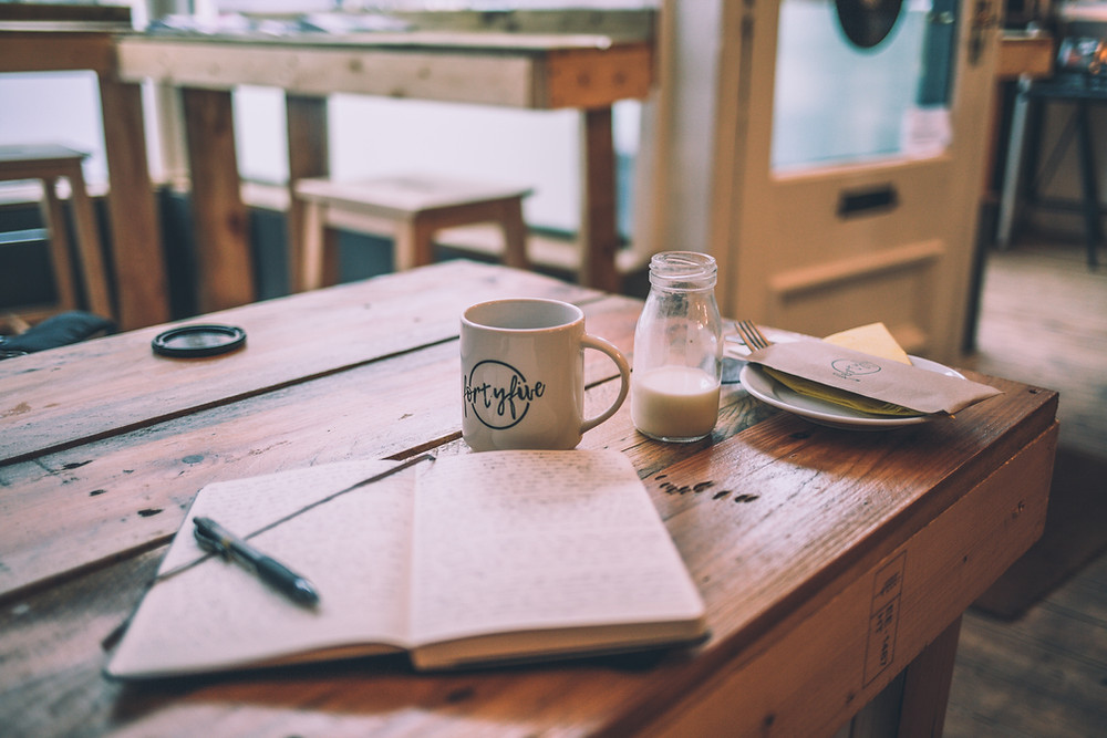 An open notebook with a pen is on a table. A jar, a  are all near. cup and a plate
