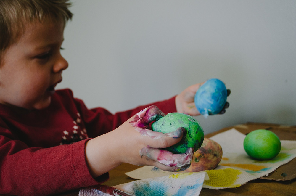 A young boy plays with coloured balls of play dough