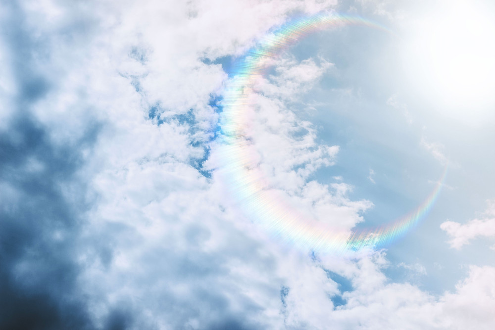the sun in a partly cloudy sky with a cirlce rainbow refraction