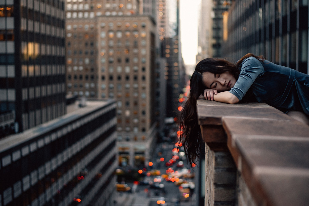 an asian woman with her upper body against a new york balcony, sleeping