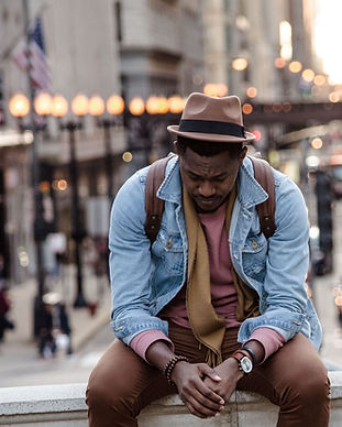 Black man sitting on ledge looking own. Image by whoislimos