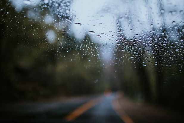 Rain on a windscreen while looking through at a road with trees either side