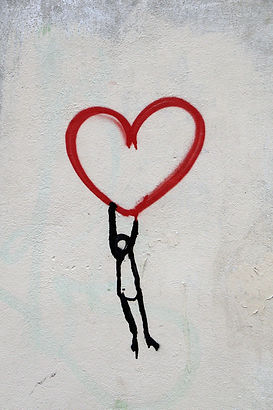 Stick figure person holding on to heart shape