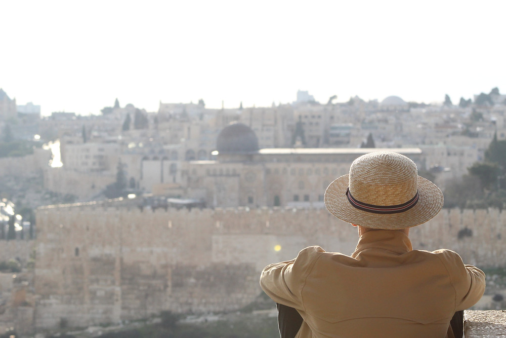 Person with a straw hat sitting on a hill overlooking Jerusalem (Yerushalyim)