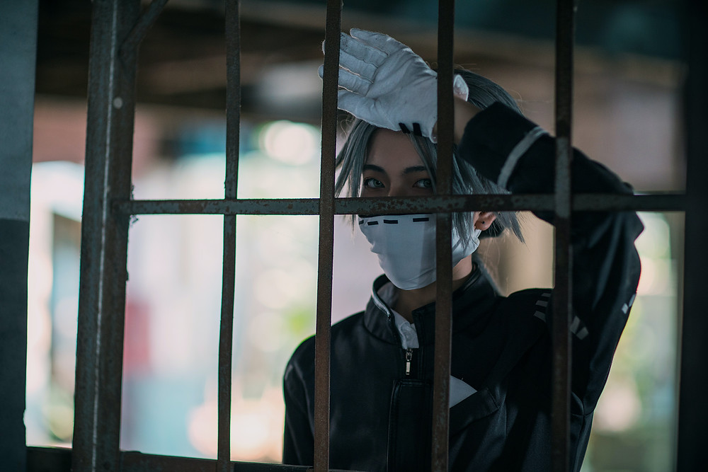 man in anime cosplay behind metal bars