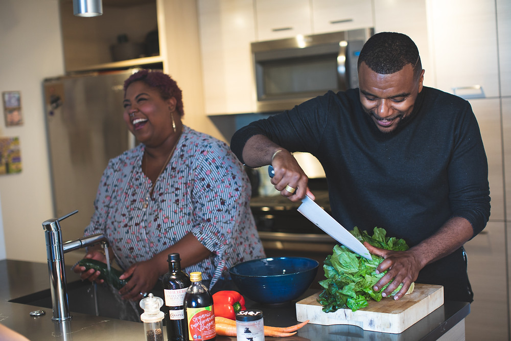 happy African American couple cooking preparing food laughing