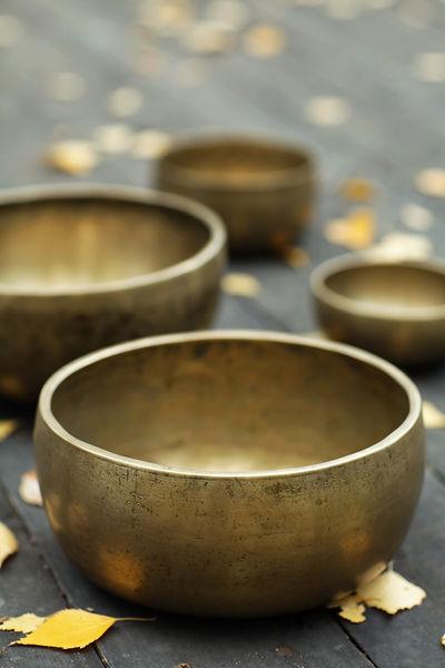 plusieurs bols tibétains pour sonothérapie, thérapie par les sons, les vibrations sonores, posés sur un sol en bois avec des feuilles d'automnes jaunes
