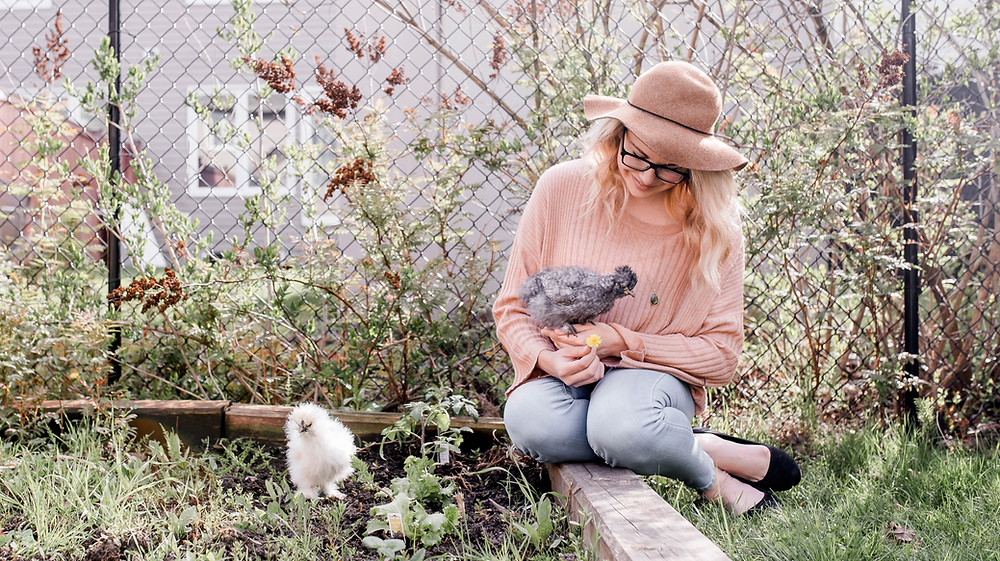 Woman sits with pet chickens in her backyard