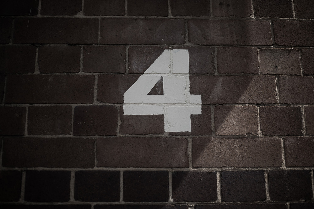 Number 4 painted on brick wall