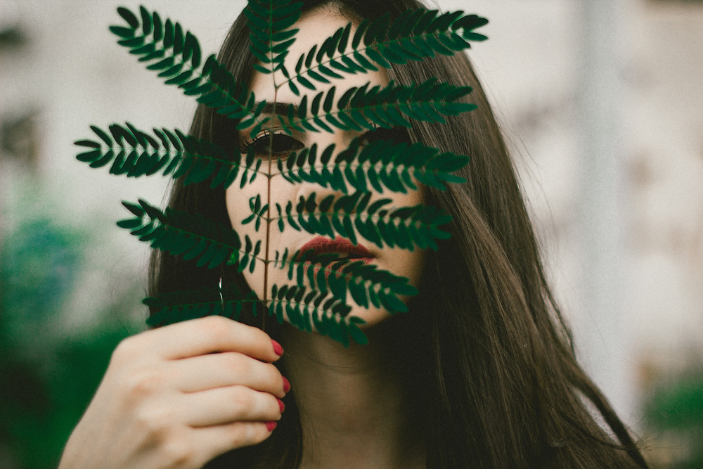 A beautiful Eurasian woman holding a green fern leaf in front of her face