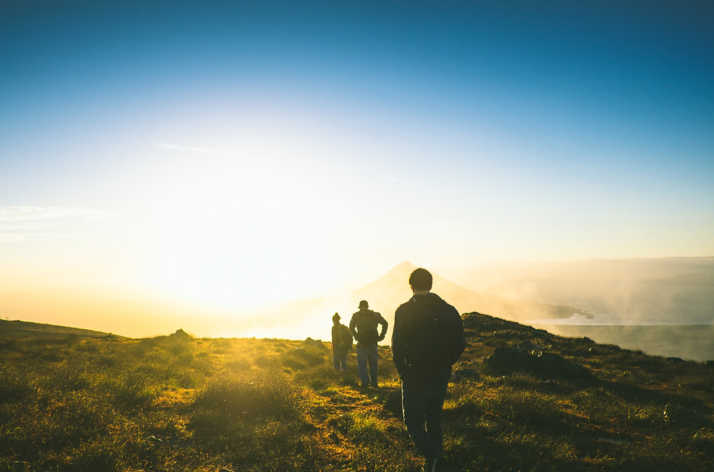 Wandernde Gruppe bei Sonnenaufgang.