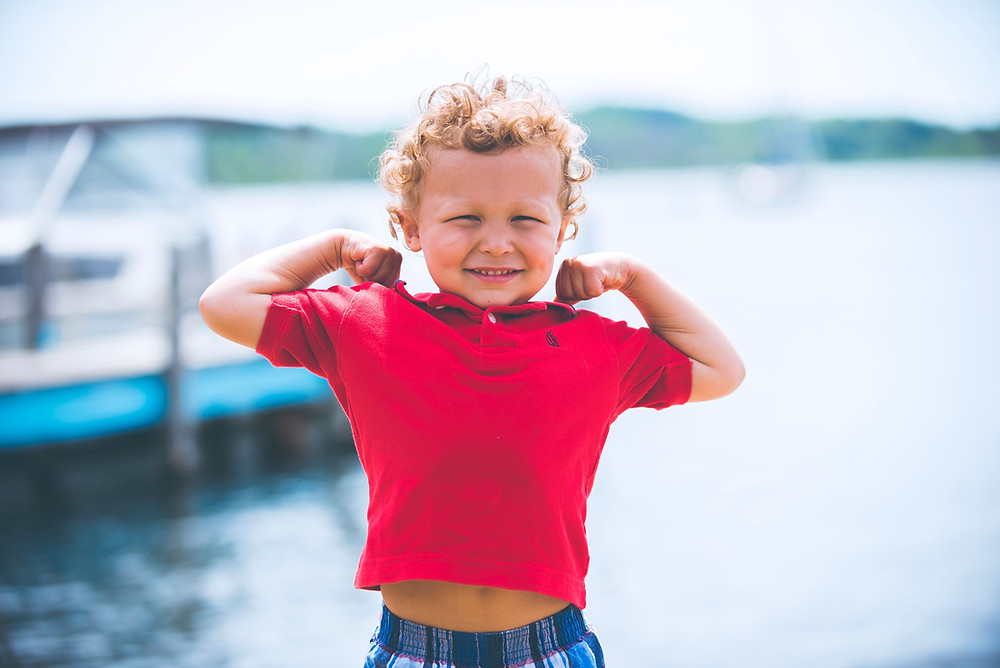 a child in a red tshirt shows his strong muscles next to some water