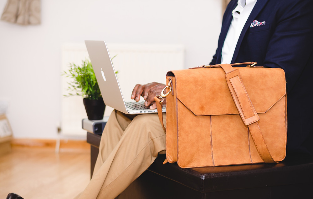 Man sitting with laptop and bag