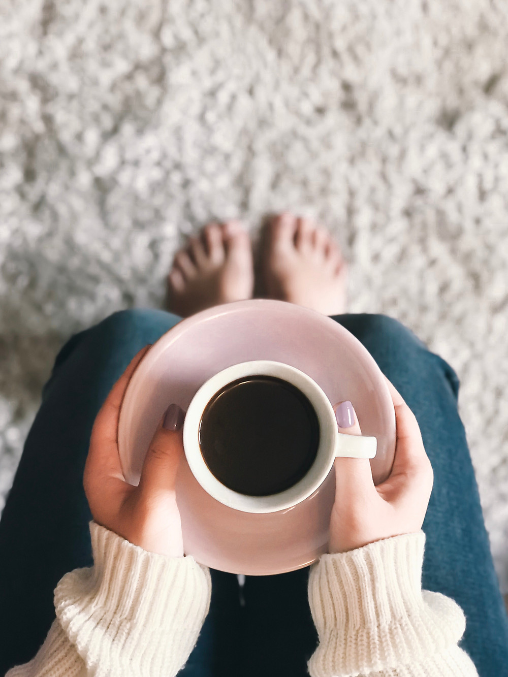 woman holding coffee cup in her lap