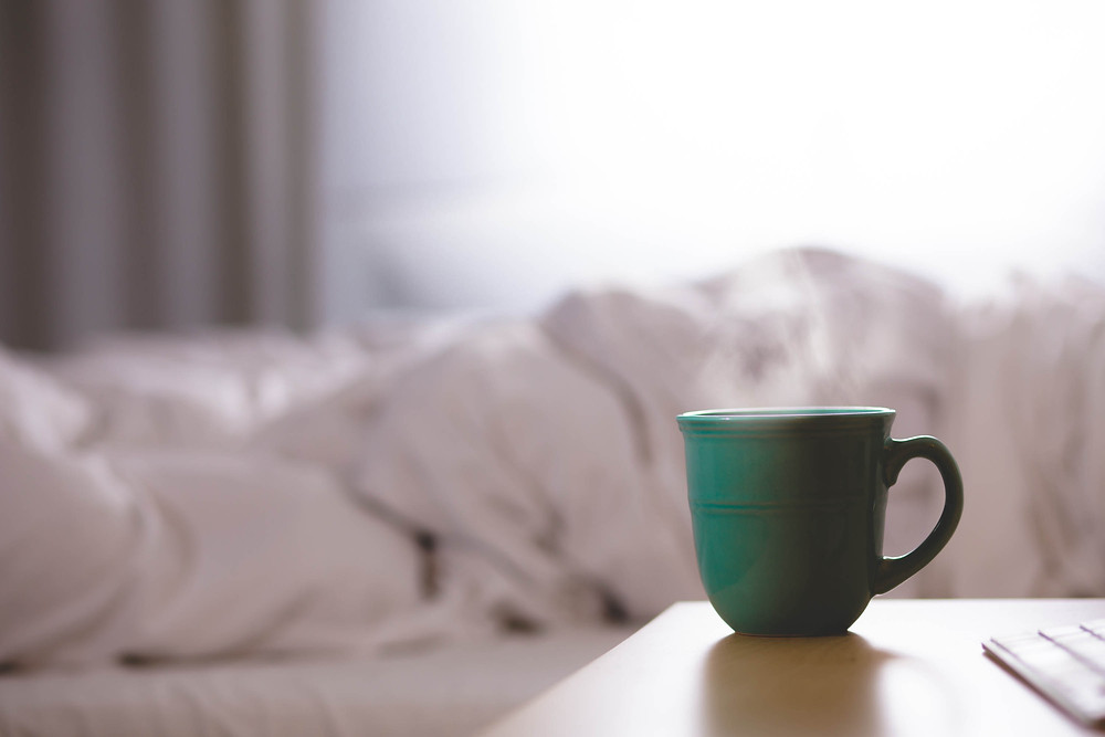 image of a green tea cup next to a messy bed