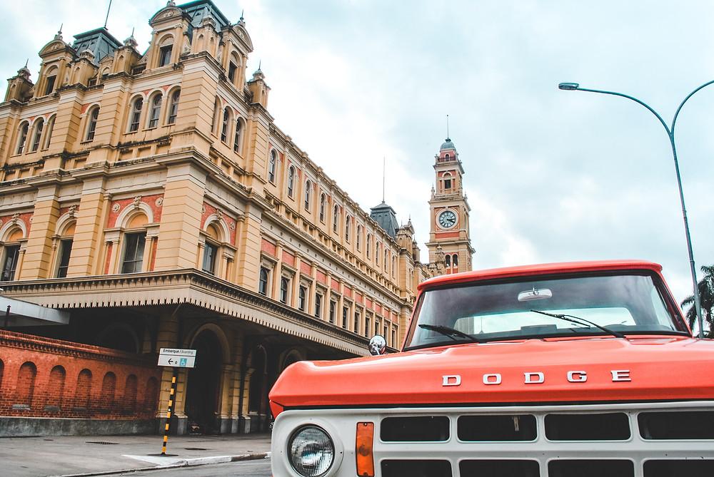 Carro antigo vermelho em frente a um prédio histórico