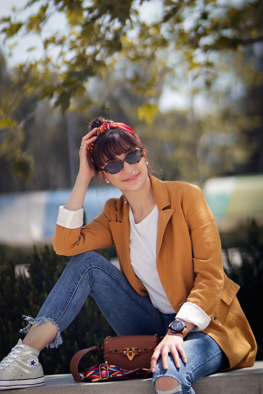 stylish woman wearing jeans sunglasses and a blazer sitting down